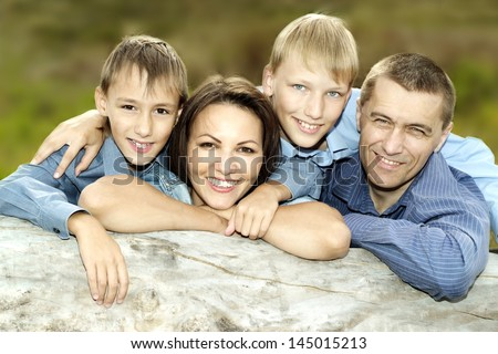 happy nice family posing outdoors in summer