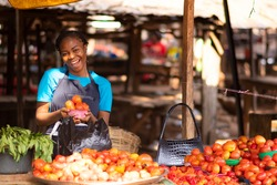 happy nigerian trader in a local market holding a bowl of tomatoes