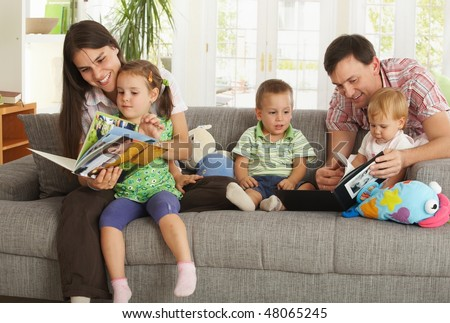 Happy nuclear family with three children having fun sitting on sofa at home, reading books, smiling.