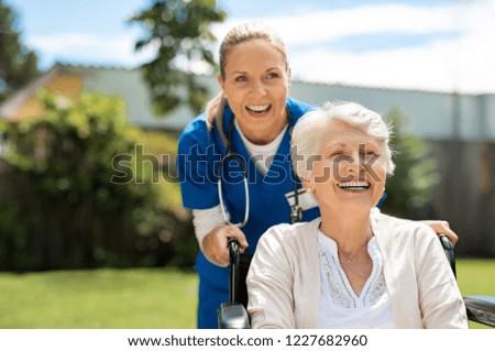 Happy nurse and elderly woman sitting in wheelchair enjoying outdoor. Beautiful nurse with laughing senior woman in wheelchair at outdoor park. Smiling disabled old lady in wheelchair at park.