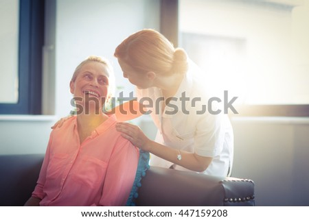 Happy nurse and patient in living room at home
