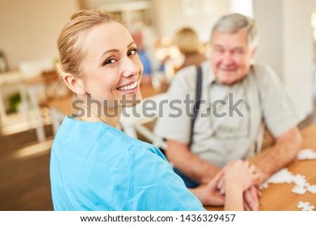 Happy nursing woman on a home visit comforts a senior man