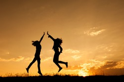Happy of two women jumping and sunset silhouette with copy space.