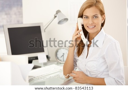 Happy office girl on landline phone call, sitting at desk, smiling at camera.?
