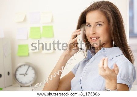 Happy office worker girl on landline call, smiling and gesturing.?