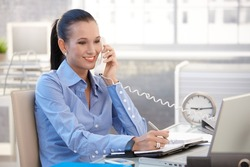 Happy office worker girl on landline phone call, smiling, listening to conversation.?