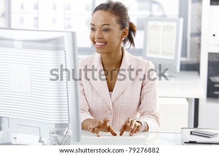 Happy office worker girl sitting at desk, working on computer, looking at screen.?