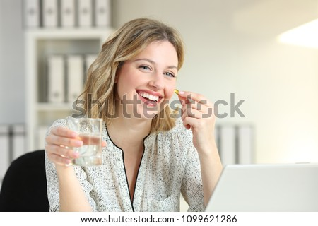 Happy office worker showing a vitamin supplement pill and a water glass looking at camera