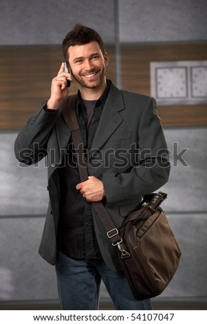 Happy office worker standing in lobby holding laptop bag talking on mobile phone smiling.