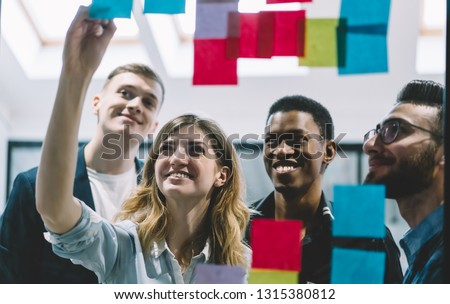 Happy office workers smiling while female colleague writing ideas on sticky notes during meeting, group of successful cheerful employees enjoying working process, collaboration and brainstorming