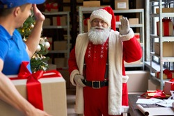 Happy old bearded Santa Claus waving hand to courier delivering Christmas present parcel on xmas eve standing in workshop. Male deliveryman holding gift box, fast express shipping delivery concept.