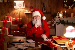 Happy old bearded Santa Claus wearing hat, looking at camera on Christmas eve showing shh secret be quiet gesture sitting at cozy home table late with presents, xmas tree, preparing for holidays.