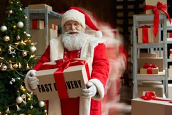 Happy old bearded Santa wearing costume hurry in blur motion to deliver gifts on xmas eve holding present standing in workshop warehouse, fast speed express delivery, Merry Christmas rush concept.