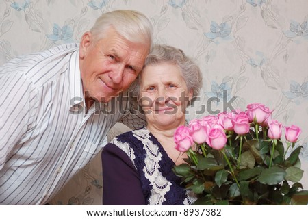 happy old couple and big bouquet of pink roses