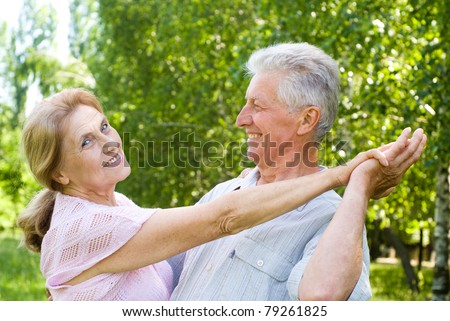 happy old couple dancing at the park