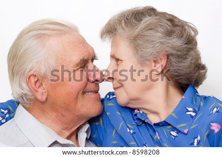 happy old couple look each other eyes nose to nose - stock photo