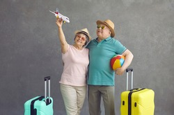 Happy old couple making dream come true. Smiling senior tourists in sunglasses and sun hats holding paper passenger airplane standing on grey studio background. Air flight and sea beach holiday