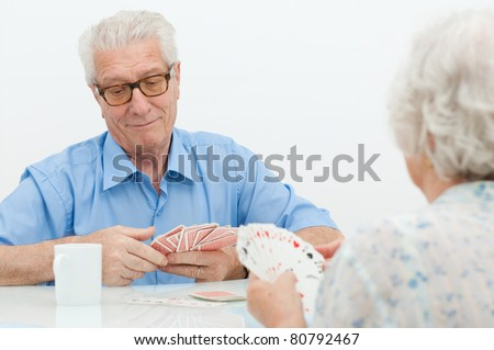 Happy old couple playing together with  cards at home