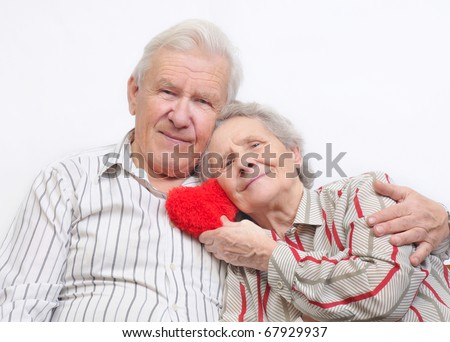 happy old couple with red heart on white background