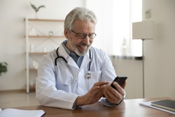 Happy old doctor holding smart phone texting message video calling for online telemedicine consultation in medical office. Smiling senior male physician using mobile healthcare app on cell technology.
