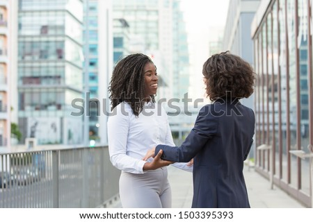 Happy old female friends accidently meeting in business district. Business women standing in city street and hugging. Surprise or meeting concept #1503395393