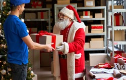 Happy old funny bearded Santa Claus wears costume holding Merry Christmas present giving gift box to courier worker delivering parcel standing in workshop. Xmas fast express shipping delivery concept
