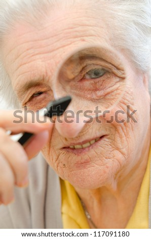 Happy old gray-haired woman with magnifier