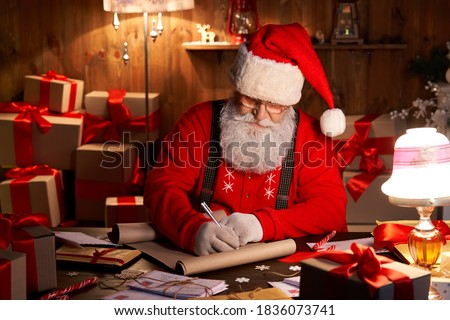 Happy old kind bearded Santa Claus wearing hat, glasses, writing on wish list, working on Christmas eve sitting at cozy home workshop table late with presents, tree and candles preparing for holidays.