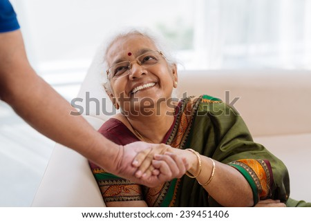 Happy old lady holding a hand of her husband and looking at him