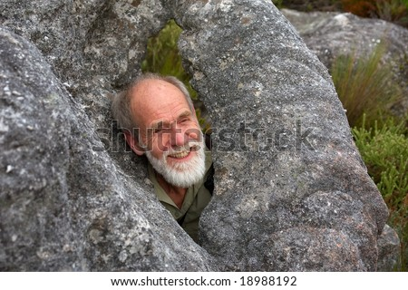 Happy old man in rocky 'window'. Shot on Stellenbosch Mountain, Western Cape, South Africa.