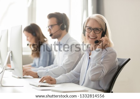 Happy old mature female call center agent telemarketer looking at camera at work, smiling aged woman telesales operator in wireless headset with computer in customer service support office, portrait