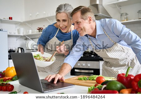 Happy old middle aged 50s couple using laptop computer preparing healthy food diet vegetable salad at home together, searching recipes, ordering shopping online, watching cooking class in kitchen.