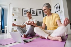 Happy old middle aged senior 50s couple learning to meditate at home watching live online tv yoga class tutorial on website looking at laptop computer doing virtual training fitness workout exercises.