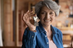 Happy old middle aged sincere beautiful hoary woman showing keys in hands, feeling excited of buying apartment or selling successfully dwelling, older people and real estate agency service concept.
