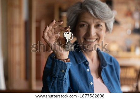 Happy old middle aged sincere beautiful hoary woman showing keys in hands, feeling excited of buying apartment or selling successfully dwelling, older people and real estate agency service concept. Сток-фото ©
