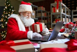 Happy old Santa Claus wearing costume holding gift box using laptop computer sitting at workshop table on Merry Christmas eve. Ecommerce website xmas time holiday online shopping sale concept.