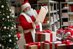 Happy old Santa Claus wearing hat and costume holding parchment roll reading letter wish list preparing Christmas shipping delivery gifts packing presents parcels standing in workshop on xmas eve.