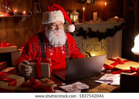 Happy old Santa Claus wearing hat holding gift box using laptop computer sitting at workshop home table late on Merry Christmas eve. Ecommerce website xmas time holiday online shopping e commerce sale