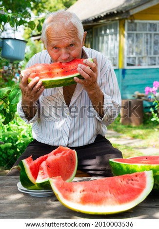 happy old señor takes a bite of watermelon in the garden of a country estate Foto stock ©