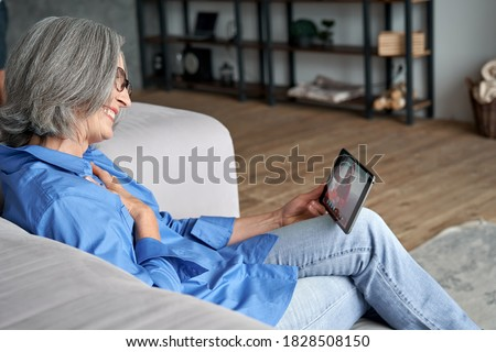 Happy old senior grandmother holding digital tablet computer in hands video conference calling granddaughter opening Christmas gift talking via distance virtual family online chat meeting at home.