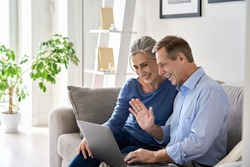 Happy old senior grandparents couple waving hand making online video call enjoying family virtual meeting digital webcam videocall chat talking, looking at laptop computer sitting on couch at home.