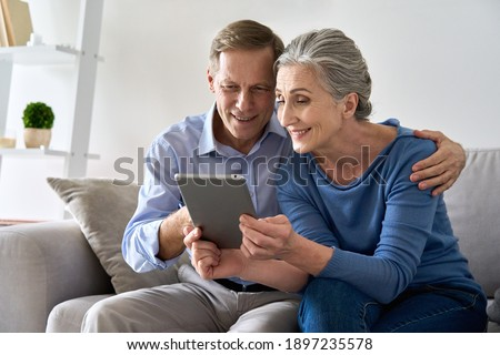 Happy old senior retired grandparents using digital tablet sitting on couch at home. Smiling mature 50s family couple enjoying websurfing online holding computer technology device making video call.