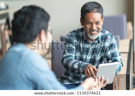 Happy old short beard asian man sitting, smiling and listen to partner that showing presentation on smart digital tablet. Mature man with social media technology teaching or urban lifestyle concept. #1134374621