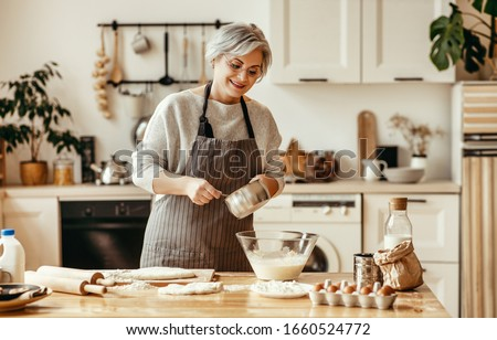 happy old woman Granny cooks in kitchen kneads dough and bakes cookies