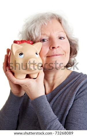 Happy old woman holding a piggy bank to her cheek
