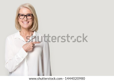 Happy old woman in glasses showing to copyspace blank space. Smiling elderly female looking at camera holding finger point to left to empty place for text. Studio portrait isolated on gray background