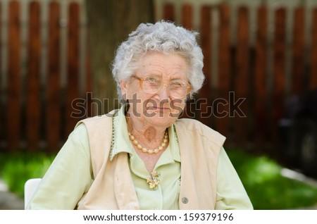 Happy old woman sitting and relaxing in the nature
