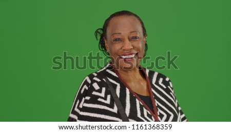 Happy older black woman poses for a portrait on green screen stock photo