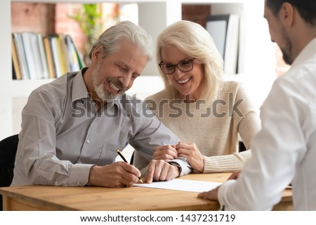 Happy older family couple clients make sale purchase deal sign insurance contract meeting estate agent lawyer bank manager, satisfied senior customers make business financial deal buy house take loan
