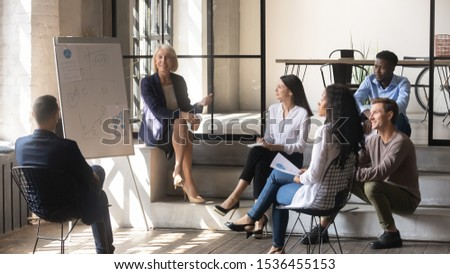 Happy older female mentor and diverse business team discuss presentation in modern office, middle aged mature businesswoman leader coach training young multiracial workers group at corporate meeting